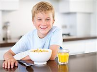 Boy having breakfast of cereal and juice Stock Photo - Premium Royalty-Freenull, Code: 635-03577406
