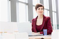 Smiling businesswoman using laptop Stock Photo - Premium Royalty-Freenull, Code: 635-03577718