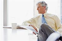 Businessman with coffee and newspaper looking away Stock Photo - Premium Royalty-Freenull, Code: 635-03577777