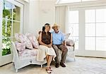 Smiling senior couple sitting on sofa Stock Photo - Premium Royalty-Freenull, Code: 635-03577855