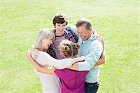 Smiling family hugging in circle on grass Stock Photo - Premium Royalty-Freenull, Code: 635-03578002
