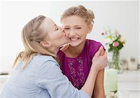 preteen kissing - Mother kissing smiling daughter in kitchen Stock Photo - Premium Royalty-Freenull, Code: 635-03578030