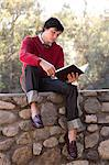 Student Reading Book and Sitting on Stone Wall Stock Photo - Premium Royalty-Free, Artist: Jerzyworks, Code: 621-03597791