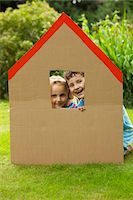 Boy and Girl Looking Out from the Window of Cardboard Cut Out in Shape of House Stock Photo - Premium Rights-Managednull, Code: 822-03601648