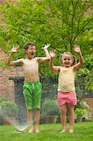 Boy and Girl Playing with Sprinkler Stock Photo - Premium Rights-Managednull, Code: 822-03601674