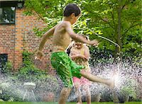 Boy and Girl Playing with Sprinkler Stock Photo - Premium Rights-Managednull, Code: 822-03601690