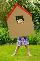Girl Looking Out from the Window of Cardboard Cut Out in Shape of House Stock Photo - Premium Rights-Managednull, Code: 822-03601705