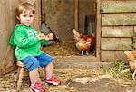 Boy Sitting Outside Chicken Coop Holding Eggs