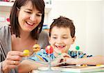 Woman and Young Boy Looking at Solar System Model Stock Photo - Premium Rights-Managed, Artist: ableimages, Code: 822-03601742