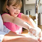 Girl Washing Hands under Running Water in Kitchen Sink Stock Photo - Premium Rights-Managed, Artist: ableimages, Code: 822-03602112