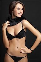 Young woman standing in black underwear, smiling Stock Photo - Premium Royalty-Freenull, Code: 618-03611435