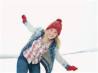 A young woman wearing a red woolen hat and gloves playing in the snow Stock Photo - Premium Royalty-Freenull, Code: 618-03612583