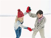 A young couple playing together in the snow Stock Photo - Premium Royalty-Freenull, Code: 618-03612584