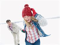 A young couple running through the snow holding hands Stock Photo - Premium Royalty-Freenull, Code: 618-03612585