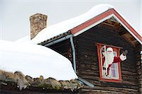 Santa Claus waving from the window of his log cabin Stock Photo - Premium Royalty-Freenull, Code: 618-03612634