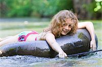 A young girl floating down a river on an inflatable ring Stock Photo - Premium Royalty-Freenull, Code: 618-03612882