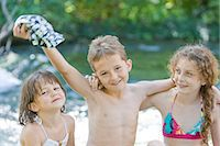 Three children in swimwear standing next to a river Stock Photo - Premium Royalty-Freenull, Code: 618-03612889