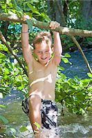 A young boy swinging from a branch over a river Stock Photo - Premium Royalty-Freenull, Code: 618-03612891