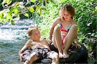 preteen girl wet clothes - Two children floating down a river together on an inflatable ring Stock Photo - Premium Royalty-Freenull, Code: 618-03612893