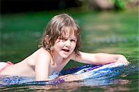 A young girl floating on a body board Stock Photo - Premium Royalty-Freenull, Code: 618-03612896