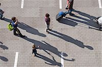 person walking on parking lot - A group of people walking through a parking lot Stock Photo - Premium Royalty-Freenull, Code: 653-03613216