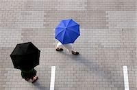 person walking on parking lot - Two women with umbrellas walking through a parking lot Stock Photo - Premium Royalty-Freenull, Code: 653-03613224
