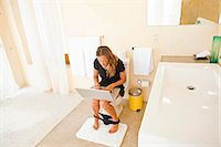 woman on laptop in bathroom Stock Photo - Premium Royalty-Freenull, Code: 673-03623288