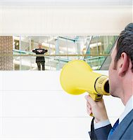 Businessman with bullhorn yelling up at boss Stock Photo - Premium Royalty-Freenull, Code: 635-03641979