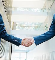 Businessmen shaking hands in lobby Stock Photo - Premium Royalty-Freenull, Code: 635-03642018