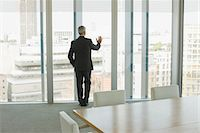 Businessman standing at window of empty conference room Stock Photo - Premium Royalty-Freenull, Code: 635-03642029