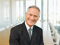 Smiling businessman in empty conference room Stock Photo - Premium Royalty-Freenull, Code: 635-03642036