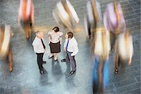 People rushing past business people talking Stock Photo - Premium Royalty-Freenull, Code: 635-03642107