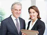 Smiling business people holding files in office Stock Photo - Premium Royalty-Freenull, Code: 635-03642183
