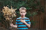 Portrait of Little Boy Holding a Plant, Houston, Texas, USA