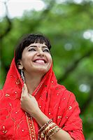 singapore traditional costume lady - Indian woman looking up and smiling with red sari over her head. Stock Photo - Premium Rights-Managednull, Code: 849-03645633