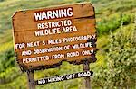 A chewed sign warns about the presence of Grizzly bears near the park road at the base of Sable Pass in Denali National Park & Preserve, Interior Alaska, Summer Stock Photo - Premium Rights-Managed, Artist: AlaskaStock, Code: 854-03646401
