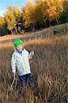 Female toddler wearing a green hat plays with driftwood sticks on the mud flats next to the Tony Knowles Coastal Trail, Anchorage, Southcentral Alaska, Fall Stock Photo - Premium Rights-Managed, Artist: AlaskaStock, Code: 854-03646458