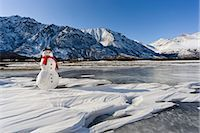 Snowman with a red scarf and black top hat sitting on the frozen Nenana River with the Alaska Range foothills in the background, Southcentral Alaska, Winter Stock Photo - Premium Rights-Managednull, Code: 854-03646502