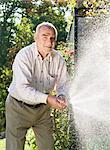 Man with water hose Stock Photo - Premium Royalty-Free, Artist: Masterfile, Code: 698-03656414