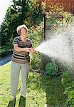 Woman with water hose Stock Photo - Premium Royalty-Free, Artist: Science Faction, Code: 698-03656415