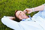 Man lying in the grass with cellphone Stock Photo - Premium Royalty-Free, Artist: Aflo Relax, Code: 698-03657615