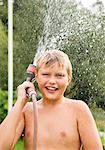 Boy holding water hose Stock Photo - Premium Royalty-Free, Artist: Aflo Relax, Code: 698-03657897