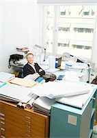 Man sitting in organized chaos Stock Photo - Premium Royalty-Freenull, Code: 698-03670111