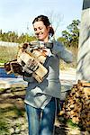 Young woman carrying wood in her arms Stock Photo - Premium Royalty-Free, Artist: Arcaid, Code: 698-03670557