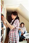 Woman getting book from bookcase Stock Photo - Premium Royalty-Free, Artist: Blend Images, Code: 698-03670665