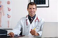 Doctor in his office with circulatory system chart and laptop Stock Photo - Premium Royalty-Freenull, Code: 644-03672143