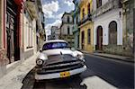 Old American Plymouth car parked on deserted street of old buildings, Havana Centro, Havana, Cuba, West Indies, Caribbean, Central America