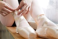 Girl tying ballet shoes Stock Photo - Premium Royalty-Freenull, Code: 614-03684402