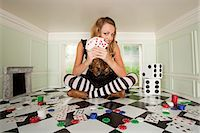 Young woman in small room with playing cards and dice Stock Photo - Premium Royalty-Freenull, Code: 614-03684540