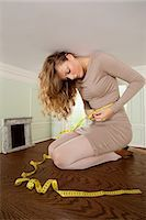 Young woman in small room measuring her waist Stock Photo - Premium Royalty-Freenull, Code: 614-03684562